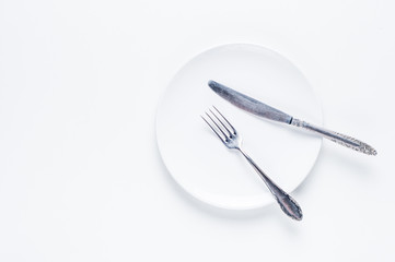 Empty white ceramic plate, knife and fork on a white background