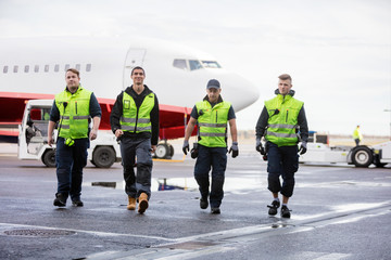 Confident Workers Walking On Runway During Rainy Season
