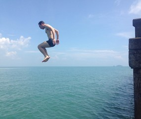 man jumping to water of sea