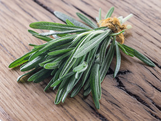 Bunch of rosemary herb on the wooden table.