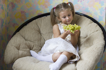 beautiful little girl sitting in the chair with grapes in hand