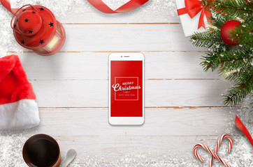 Hero header Christmas scene with mobile phone in the middle wih Merry Christmas message. Christmas tree, gifts, decorations on white wooden desk.