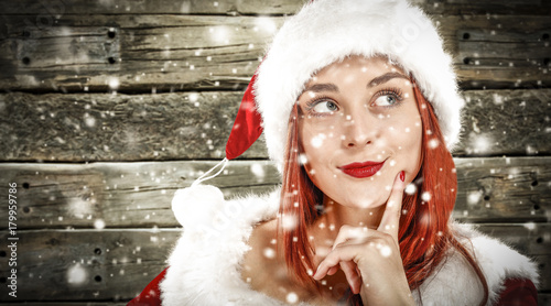 d70d79f6a91b6 A beautiful young woman in a Santa Claus hat. Dressed in red costume.  wooden wall background. In the foreground snow and snowflakes are in the  foreground.