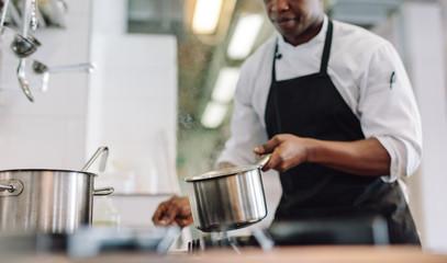 Chef cooking food at restaurant kitchen