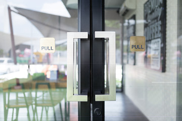 Restaurang door handle with pull sign on glass doors