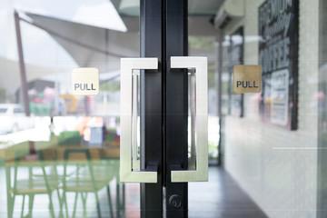 Restaurang door handle with pull sign on glass doors