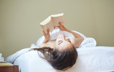portrait of young woman lies in bed early in the morning. woman lies with book and looks up
