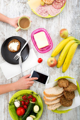 A woman's hand with food and phone