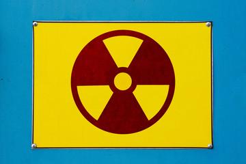Closeup view of radioactive hazard sign. Yellow board on blue metallic surface