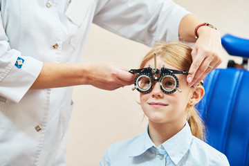 Child optometry concept. Young girl with phoropter during sight testing