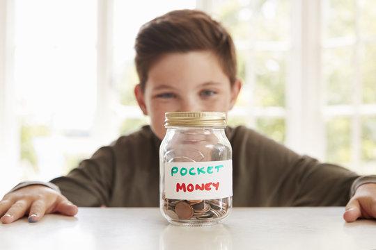 Boy Saving Pocket Money In Glass Jar At Home