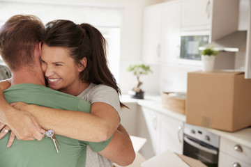 Hugging Couple Celebrating Moving Into New Home