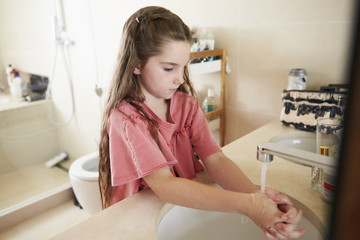 Girl Washing Hands In Bathroom Basin At Home