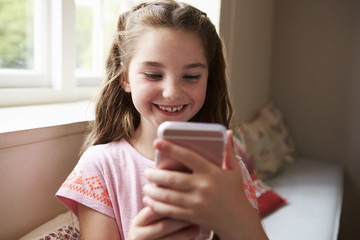 Smiling Girl Sitting On Window Seat Playing Game On Mobile Phone