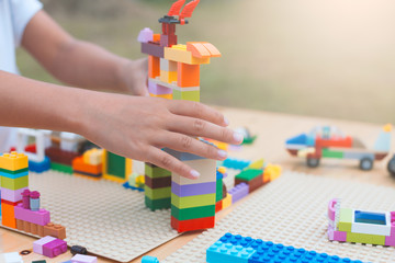 Asian little child girl hand playing with colorful blocks. She is creating and building her toy with fun in good weather outside.