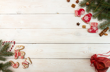 Overhead of Christmas New Year holiday background. Red gingerbread cookies elk, deer, boots, meetens, bag with gift, fir branch tree on white wooden background. Top view.