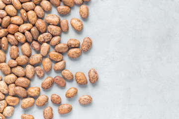 Uncooked dry pinto beans on a gray concrete background, top view, copy space