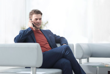 businessman talking on mobile phone sitting in a chair.