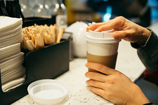 womans hand near rack with cup of coffee