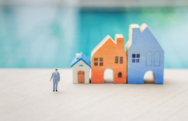 Miniature business man with blurred miniature house over blurred swimming pool background, real estate and property business concept