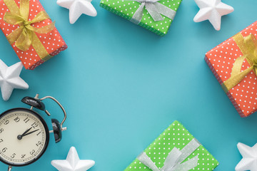 Christmas and New Year holiday composition with gift boxes, stars, clock on the blue background. Top view, flat lay. Copyspace.