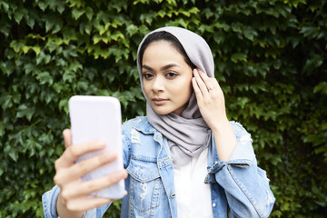 Young woman looking at her phone screen wearing hijab