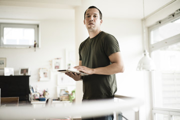 Portrait of serious man at home using tablet