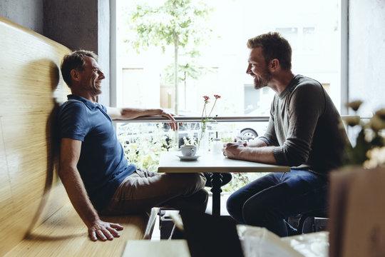 Two men sitting in cafe talking