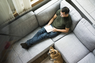 Man at home using tablet on the couch with dog beside him