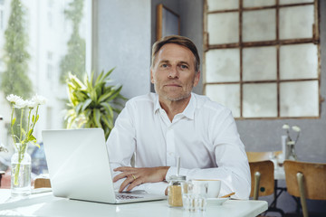 Portrait of businessman in cafe with laptop