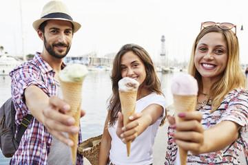 Three smiling friends holding ice cream cones