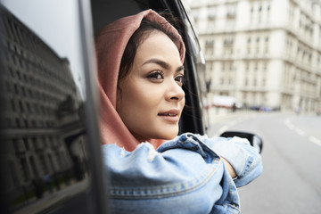 Young woman wearing hijab looking out of taxi