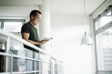 Smiling man at home using tablet on upper floor