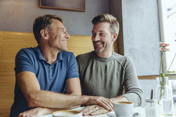 Gay couple putting their hands together with wedding rings in cafe