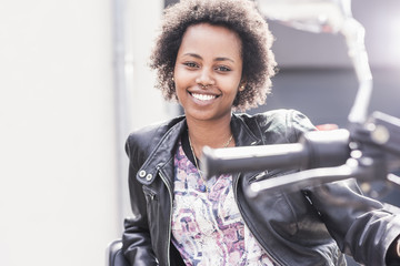 Portrait of smiling young woman with her motorcycle
