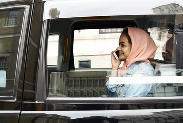 Young woman wearing hijab using phone in taxi