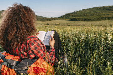 Back view of teenage girl reading book on a meadow