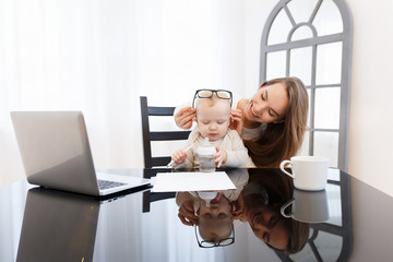 Young mother having fun and holding baby while working at laptop in home office. Business woman concept.