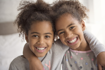 Two little african american girls on bed at home
