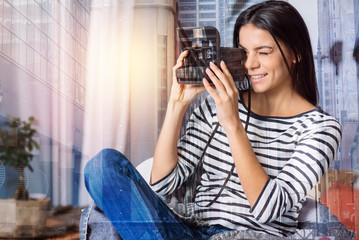Interesting hobby. Curious young woman trying to take a photo with a help of an instant photo camera while sitting in an armchair