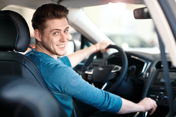 Happy young male driver behind the wheel Wall mural