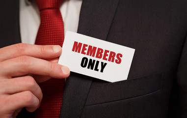 Businessman putting a card with text MEMBERS ONLY in the pocket