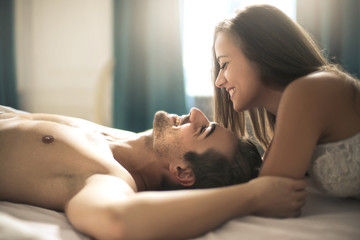 Handsome guy and beautiful woman kissing and laughing in the bed
