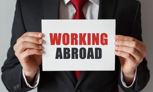 Businessman holding a card with text Working Abroad