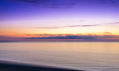 Stylized abstract landscape seascape sunset long exposure with clouds under different shades of blue, orange, yellow and red.
