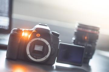 Spiegelreflexkamera mit Flipscreenund Objektiv auf Tisch, Sonnenschein
