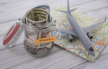 Travel budget concept. Travel money savings in a glass jar with aircraft toy on world map.
