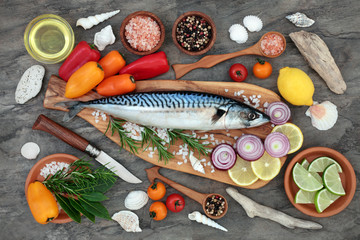 Mackerel fish health food with seasoning, vegetables and fruit on an olive wood board on marble background. High in omega 3 and beneficial for maintaining a healthy heart.