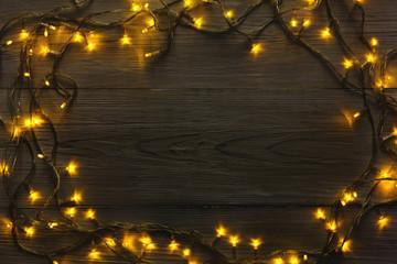 Christmas lights frame on grey wooden background