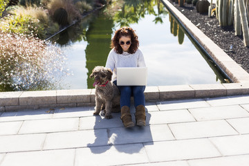beautiful young woman having fun with her cute brown dog and using laptop. Outdoors